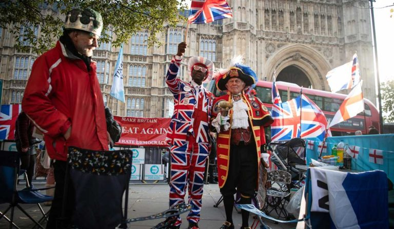 LONDON, ENGLAND - OCTOBER 31: Pro-Brexit activist Joseph Afrane (C) stands with Town crier Tony Appleton (CR) outside the Houses of Parliament on what would have been the day that the United Kingdom left the European Union if the previous delay deadline had been observed, on October 31, 2019 in London, England. A further extension has now been granted which will see a general election take place, in a bid to break the Parliamentary deadlock. (Photo by Leon Neal/Getty Images)